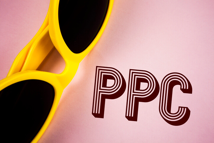 Yellow sunglasses on a pink background alongside PPC that is written next to the sunglasses